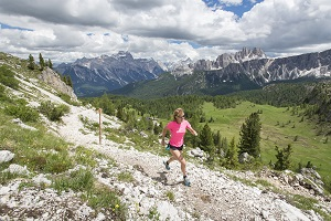 One female runner at the 5 Torri in the Dolomites, Italy during summer.
